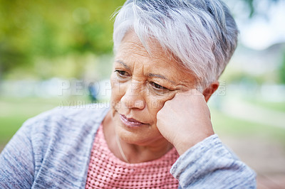 Buy stock photo Cropped shot of a retired senior woman looking stressed while in the park alone during the day