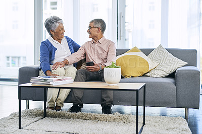 Buy stock photo Full length shot of a retired senior couple sitting together on the sofa in the living room during the day