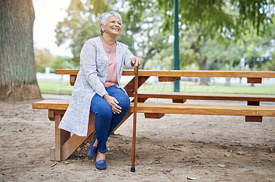 Buy stock photo Full length shot of a retired senior woman sitting at a picnic table alone in the park during the day