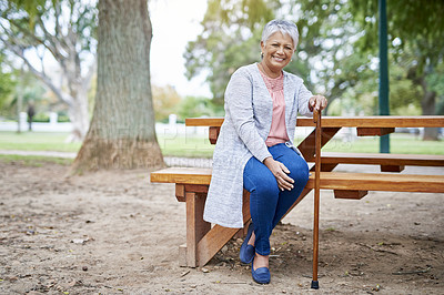 Buy stock photo Full length portrait of a retired senior woman sitting at a picnic table alone in the park during the day