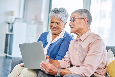 Buy stock photo Cropped shot of a happy senior couple using a laptop while sitting on the sofa together in the living room
