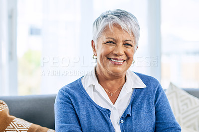 Buy stock photo Cropped portrait of a retired senior woman smiling while sitting on the sofa in the living room