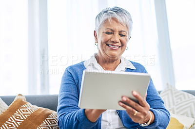 Buy stock photo Cropped shot of a retired senior woman using a tablet while sitting on the sofa in the living room