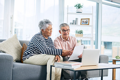 Buy stock photo Cropped shot of a senior couple working on some paperwork while sitting together on the sofa in their living room