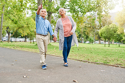 Buy stock photo Full length shot of a happy senior couple holding hands and walking through the park together during the day