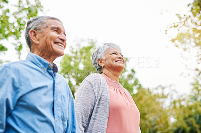 Buy stock photo Cropped shot of a happy senior couple standing closely together in the park during the day