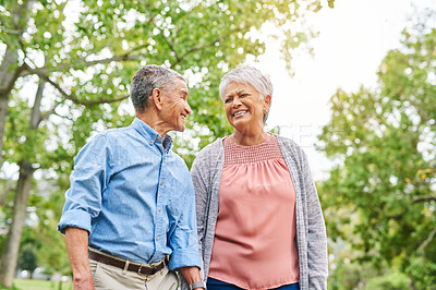 Buy stock photo Cropped shot of a happy senior couple holding hands and walking through the park together during the day