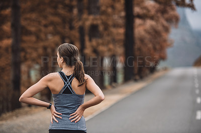 Buy stock photo Rearview shot of a sporty young woman taking a break while exercising outdoors