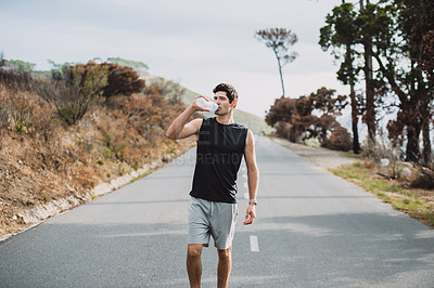 Buy stock photo Shot of a sporty young man drinking water while exercising outdoors