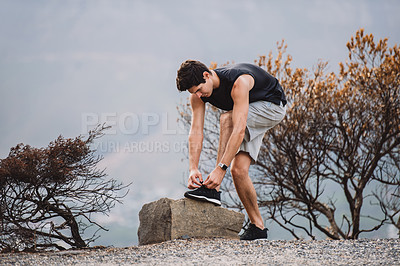 Buy stock photo Shot of a sporty young man tying his laces while exercising outdoors