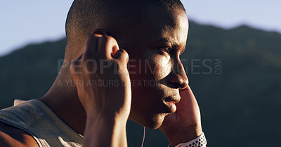 Buy stock photo Cropped shot of a young man inserting his earphones while out for a run