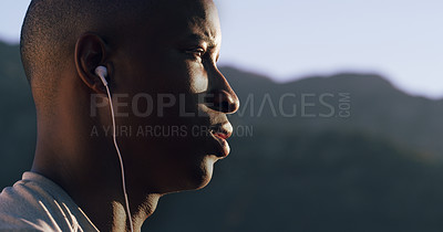 Buy stock photo Cropped shot of a young man wearing earphones while out for a run