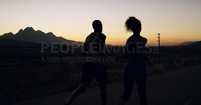 Buy stock photo Shot of two sporty young people out for a run in nature