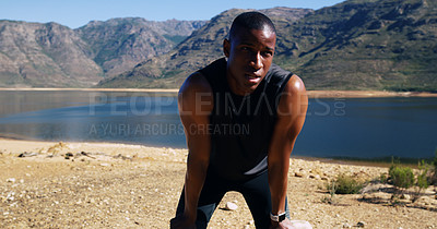 Buy stock photo Shot of a sporty young man catching his breath after a run outdoors