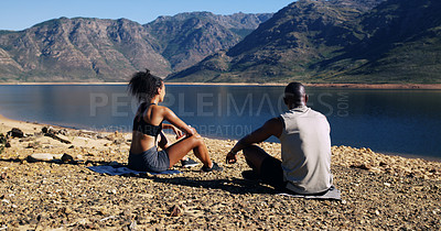 Buy stock photo Shot of a sporty young couple taking a break while out for a run in nature
