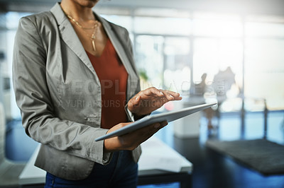 Buy stock photo Shot of an unrecognizable businesswoman using a digital tablet in an office