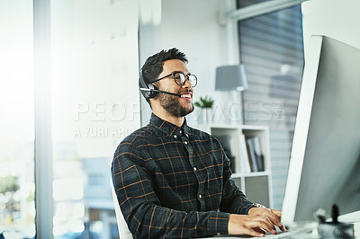 Buy stock photo Shot of a handsome young call centre agent working in his office