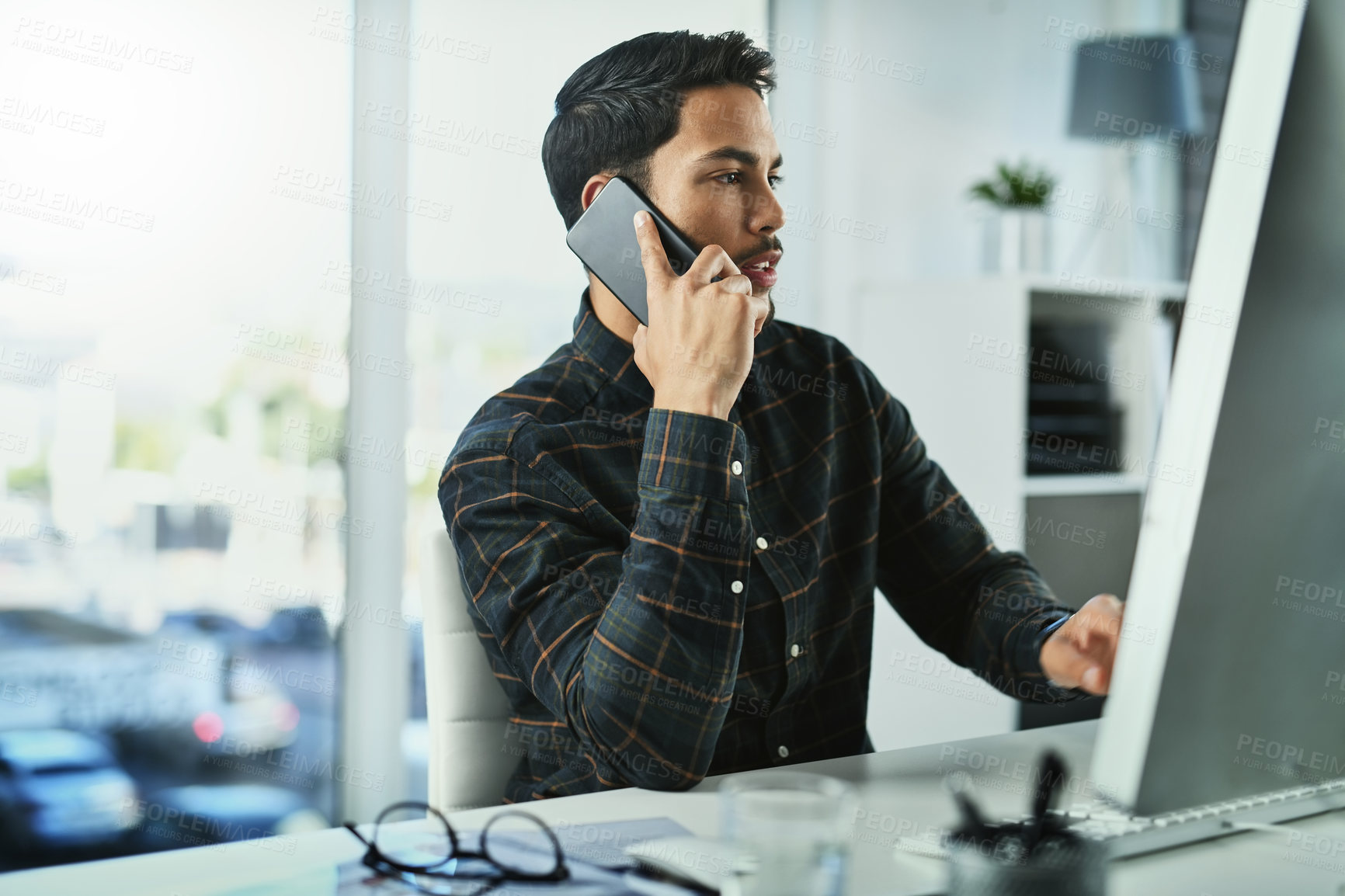 Buy stock photo Shot of a handsome young businessman taking a phone call at his office desk at work