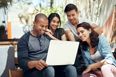 Buy stock photo Shot of a group of young men and women using a laptop together on campus