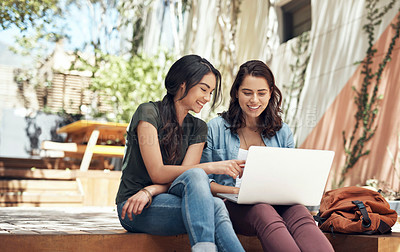 Buy stock photo Shot of two young women using a laptop together on campus