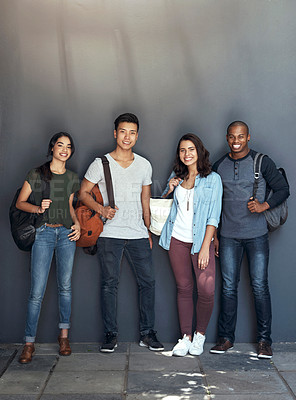 Buy stock photo Portrait of a group of young students standing together against a grey wall