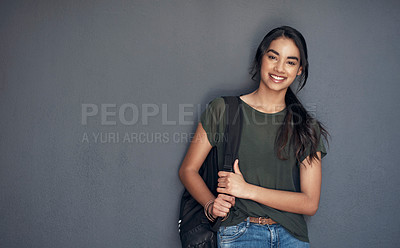 Buy stock photo Studio portrait of a young woman carrying a schoolbag against a grey background