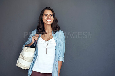 Buy stock photo Studio shot of a young woman carrying a schoolbag against a grey background