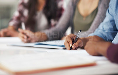 Buy stock photo Cropped shot of a group of men and women writing in their notebooks at college