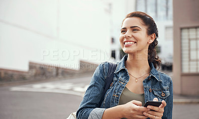Buy stock photo Shot of a happy young student using her smartphone in the city