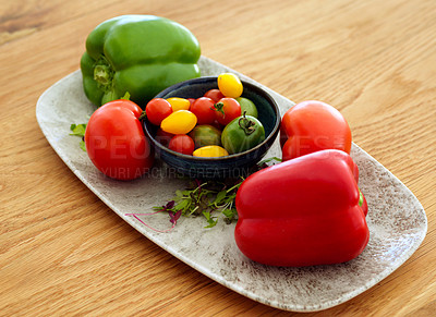 Buy stock photo Shot of brightly coloured peppers arranged on a silver dish before being cooked in the kitchen during the day