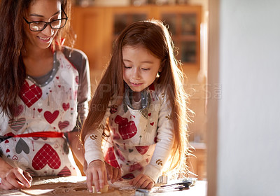 Buy stock photo Shot of a mother and her little daughter baking together at home