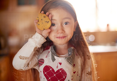 Buy stock photo Portrait of an adorable little girl holding a cookie at home