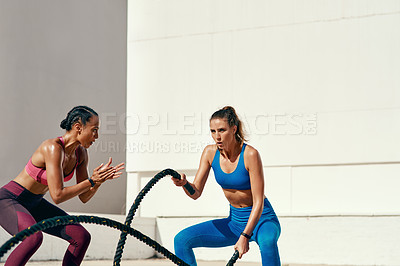 Buy stock photo Shot of sporty young woman doing heavy rope training with her trainer