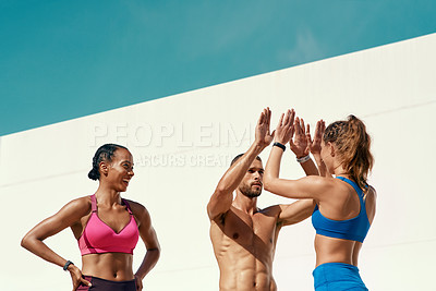 Buy stock photo Shot of sporty young people high fiving after their workout