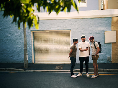 Buy stock photo Full length shot of three handsome young men standing together and using a cellphone while in the city during the day
