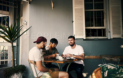 Buy stock photo Cropped shot of three handsome young men sitting together and using a cellphone during the day