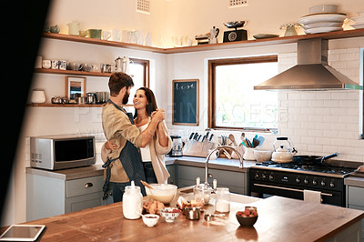 Buy stock photo Shot of a happy young couple dancing in the kitchen while preparing breakfast at home
