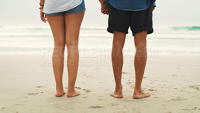 Buy stock photo Cropped rearview shot of an unrecognizable couple standing next to each other on the beach during the day