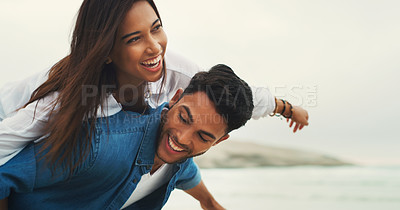 Buy stock photo Cropped shot of a playful young couple enjoying their time together on the beach during the day