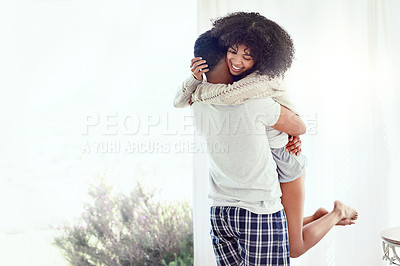Buy stock photo Rearview shot of an affectionate young man lifting his wife in their bedroom at home