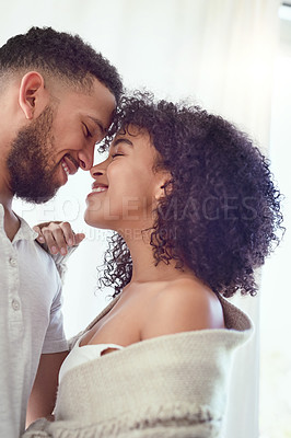 Buy stock photo Cropped shot of an affectionate young couple smiling at each other while standing in their bedroom at home
