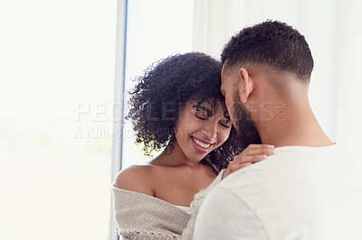 Buy stock photo Cropped shot of an affectionate young woman smiling during an intimate moment with her husband at home