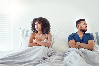 Buy stock photo Shot of a young couple acting moody towards each other after an argument in their bedroom at home