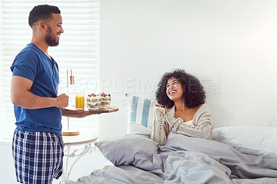 Buy stock photo Cropped shot of an affectionate young man serving his wife breakfast in bed at home