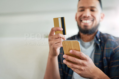 Buy stock photo Shot of a young man using a smartphone and credit card while relaxing at home