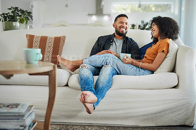 Buy stock photo Shot of a young couple enjoying a coffee break while relaxing together at home