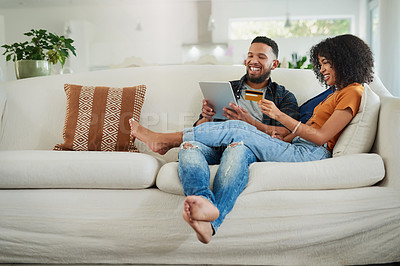 Buy stock photo Shot of a young couple using a digital tablet and credit card while relaxing at home
