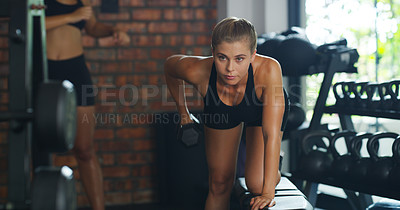 Buy stock photo Shot of a beautiful young sportswoman working out using dumbbells at the gym