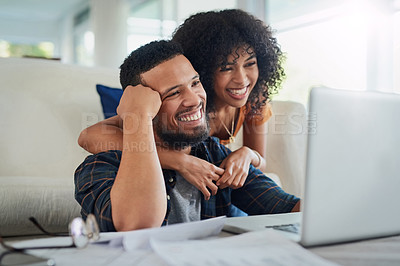 Buy stock photo Shot of a happy young couple looking going over their finances at home