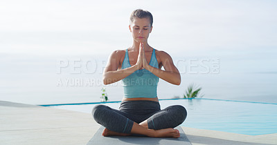 Buy stock photo Full length shot of a beautiful young woman sitting down and meditating while practicing yoga beside a swimming pool